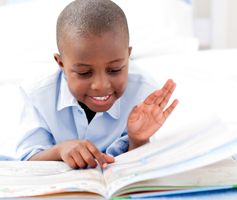 Small boy reading a book on his bed